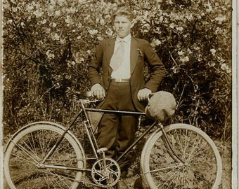 Handsome man with bicycle by blooming tree antique