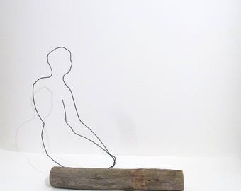 Young man sitting on Driftwood sculpture