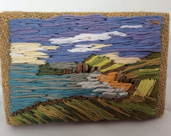 Hand embroidered picture of the seaside with rolling green hills