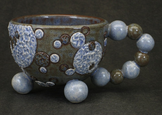 mottled blue and brown tripod mug with textured molecular motif