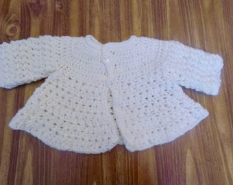 white crocheted infant sweater
