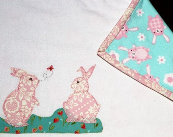 Baby blanket unique and handmade with applique rabbits in a field of flowers.  Proceeds to charity VACD Ltd