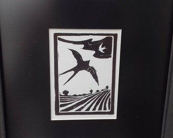 "Original lino cut print of 2 flying swallows over a field in black and white. ""Harvest Swallows"". In a vintage painted frame."