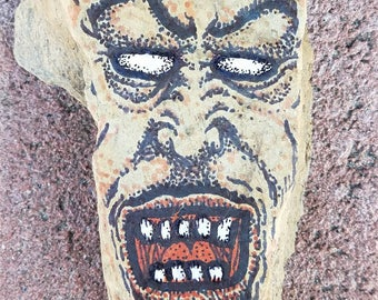 Scary face painted on a piece of slate w/ rock stand.