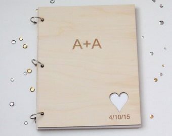 Simple wedding guest book with engraved initials and wedding date with heart cutout