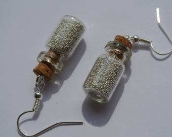 a pair of earring is silver flask