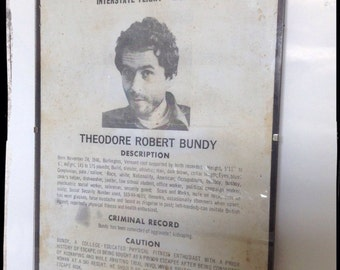 Ted Bundy wanted poster aged reproduction in clip frame.