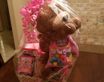 A gift basket and a personalized teddy bear withh name and birthday.