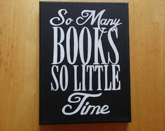 """Hand painted black canvas sign reads:""""So many books so little time"""" with white typography"""