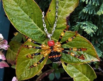 black and orange spider necklace made of beads.