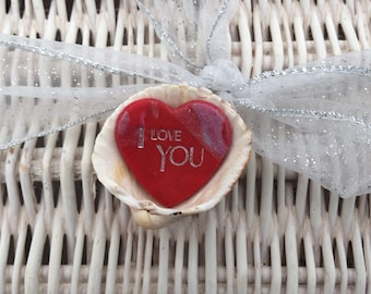 Handmade Red clay heart inscribed I Love You mounted in a cockle shell