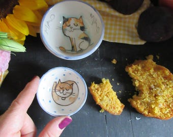 Small bowls door handmade ceramic sauces with illustrations of cats