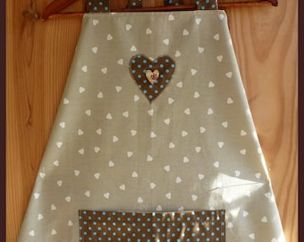 Beige apron with white hearts appliqué avecd and pouch.