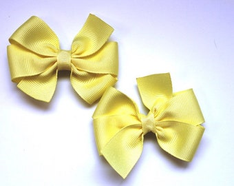 4 inch pale yellow pinwheel style bow on matching pale yellow ribbon lined alligator clip