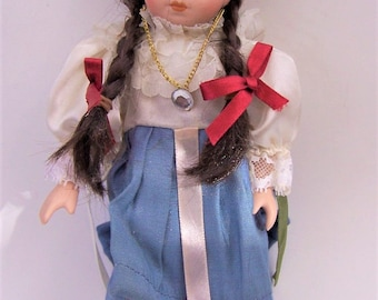 Vintage Porcelain Miniature Unbranded Doll Braided Hair with Red Ribbons, Blue Skirt, Ruffled Blouse , Pendant Necklace and Sandals