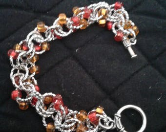 Twisted jumprings with red and orange bracelets