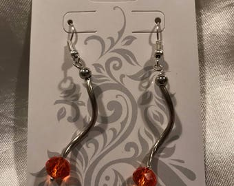 Metal swirl drop earring with orange faceted bead
