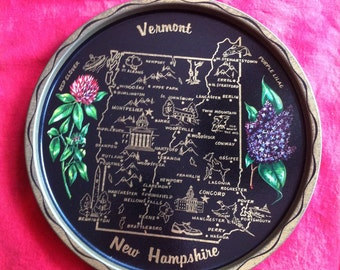 A Black Decorative Souvenir Metal Tray Of Vermont And New Hampshire