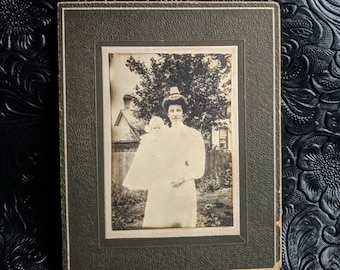 Antique cabinet card photograph of a Victorian era nurse holding a baby outdoors