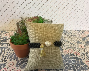 Black knitted bracelet with gold tassel and pearl