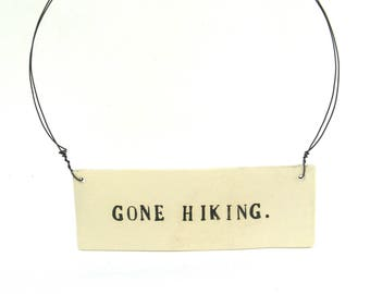 gone hiking   ...  hanging porcelain sign
