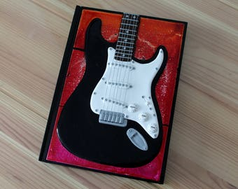Note pad with cover made of polymer clay depicting an electric guitar black and white