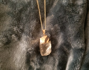 Gold edged clear crystal stone pendant with chain.