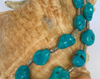 Necklace is made with turquoise and silver colored beads.