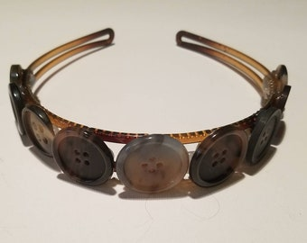 Brown plastic headband adorned with brown decorative buttons