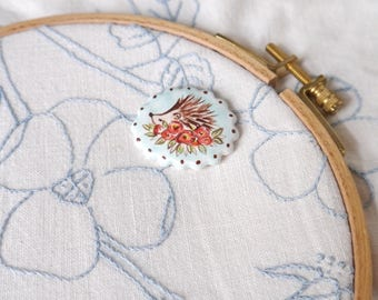 Oval Ceramic Needleminder with Painted Hedgehog and Red Roses on Blue Background