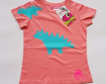 Sparkle blue stegosaurus on pink tee