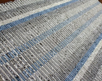 Handwoven rug in shades of gray, white and blue.