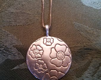 Small sterling silver pendant with flowers on it.