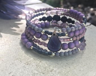 Beautiful purple wire wrap bracelet featuring lava beads for essential oils and a vivid purple colorized resin drop. Essential oil jewelry.