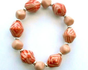 Delicate pale coral pink Kazuri fair trade ceramic bracelet with some pale red abstract design.