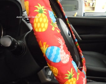 Pineapples on red steering wheel cover. Multi colored pineapples. Fully lined cover. Seat belt covers and key fob options.