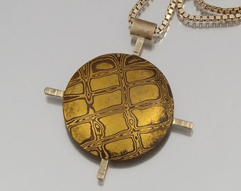 Custom mokume gane jewelry by anne wolf by annewolfmokumegane mokume gane pendant bold patterned brass and copper domed disc with sterling silver crossed bars aloadofball Gallery