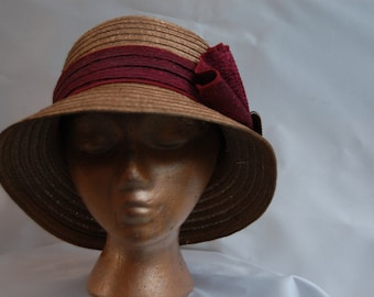 Sophisticted lady.Gold straw clouche with burbundy accent, perfect for the Derby