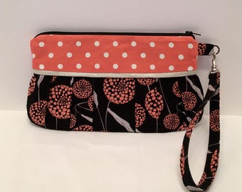 AK27- Compleat Clutch: in a modern black and orange flower print with pleated front, zipper closure and detatchable hand strap