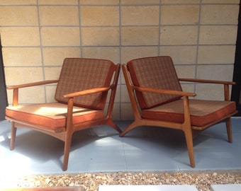 Stunning pair of mid century modern lounge chairs with vintage reversible cushions