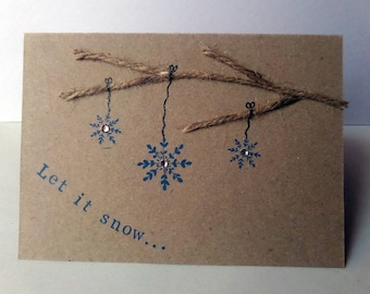 Let it snow Christmas card with snowflakes hanging from a tree branch
