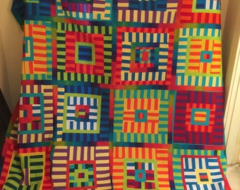 Bright scrappy full/queen quilt with a lone square on the backing.