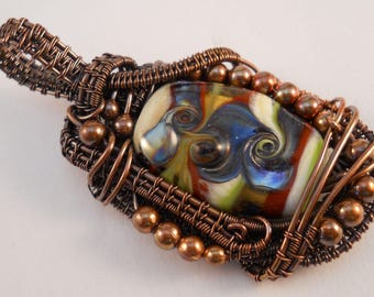 Copper wire and lampwork glass pendant in swirls of cream, metallic black, red and green with copper bead accents.