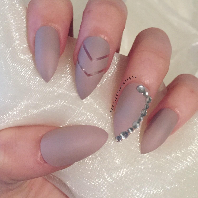 Matte nude stiletto false nails with chevron negative design