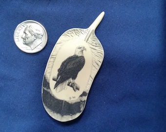 "Eagle Scrimshaw on Feather By: Hop, Reproduction Polymer Scrimshaw. 2 1/2"" tall by 1 1/8"" wide."