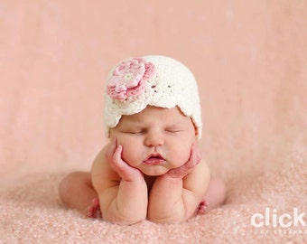 0-3 month cream flapper beanie with a pink flower
