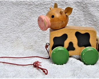 Wooden toy pig on wheels