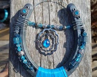 ShoesofLuck Blue topaz decorated horseshoe with blue beads.