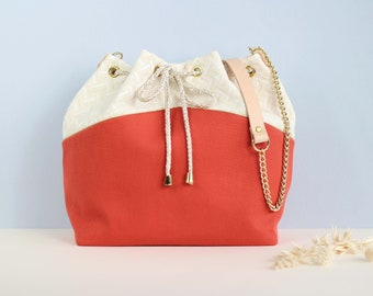Gisèle: bucket bag made of and off-white cotton, orange cotton, lurex piping and golden chain.