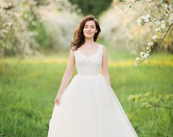 Off-white ball-gown wedding dress with sleeveless v-neck lace bodice